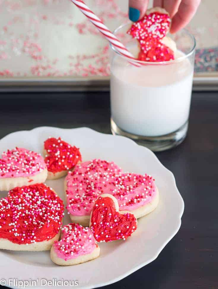 gluten free heart sugar cookies with pink and red frosting and pink, white, and red non pareil sprinkles on a white plate with a scalloped edge on a dark wooden table with a glass of milk with a hand dipping a red heart cookie with a bite taken out of it, with a white and red striped straw in the background