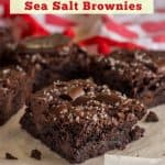 "gluten free brownies sprinkles with dark chocolate morsels and chunks and flaky sea salt on a piece of white parchment paper on a white bead-board table with a dishtowel with hearts on it in the background with text ""gluten-free dairy-free dark chocolate sea salt brownies"""
