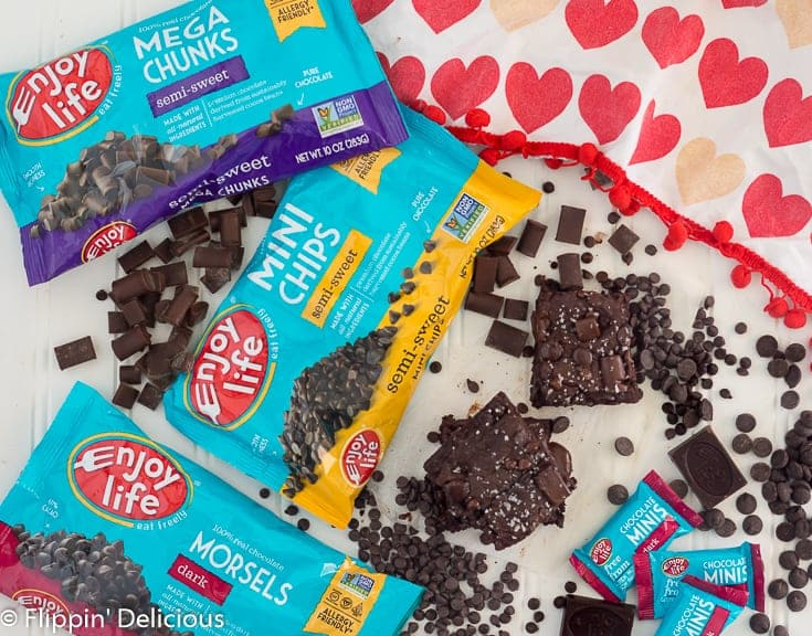 Overhead view of two gluten free brownies topped with chocolate chips and sea salt beside Enjoy Life Mega Chunks, Mini Chips, and Dark Morsels and Dark Chocolate Minis and teal packaging with a dish towel with read and peach hearts on it