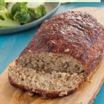 """gluten free turkey meatloaf with a slice cut off, beside the meatloaf, on a wooden cutting board with a green plate with broccoli, mashed potatoes and gluten free meatloaf in the background, on a teal wooden table with gray streaks with text """"gluten-free turkey meatloaf"""""""