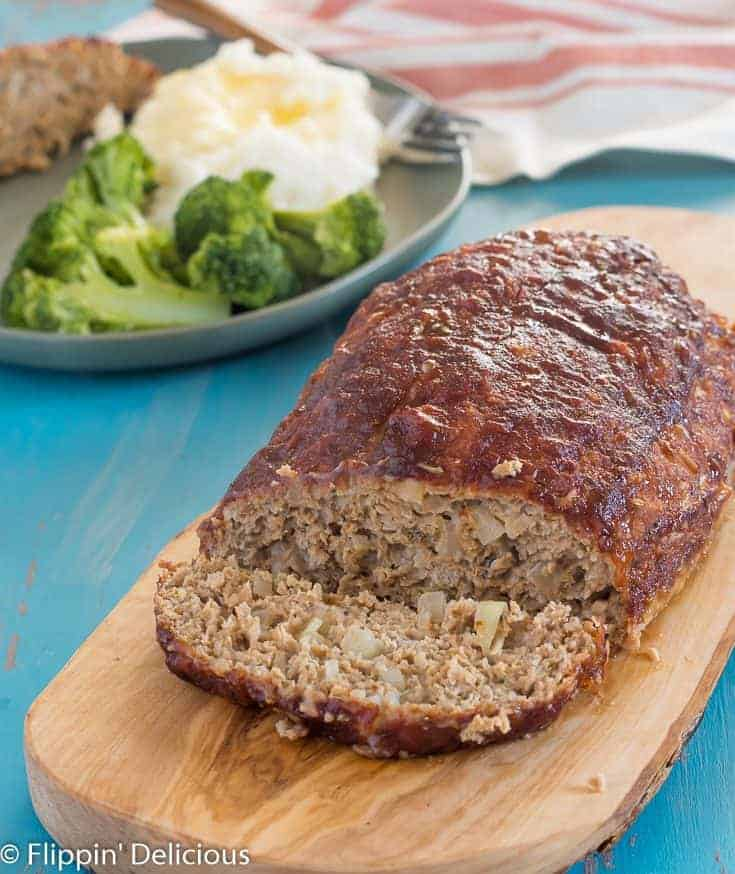 gluten free turkey meatloaf with a slice cut off, beside the meatloaf, on a wooden cutting board with a green plate with broccoli, mashed potatoes and gluten free meatloaf in the background, on a teal wooden table with gray streaks