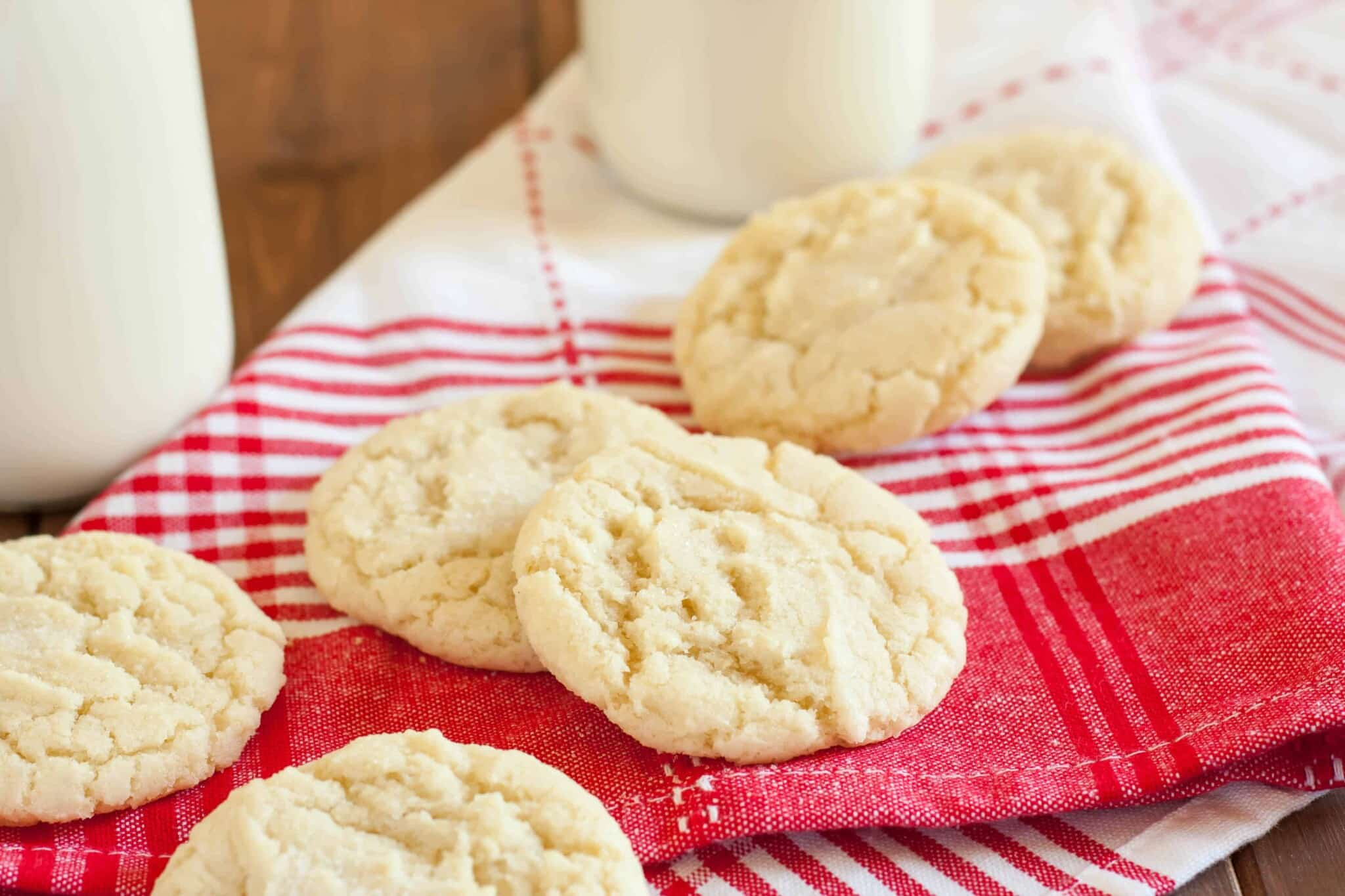 drop gluten free sugar cookies on a red and white striped napkin with a bottle of milk in the background