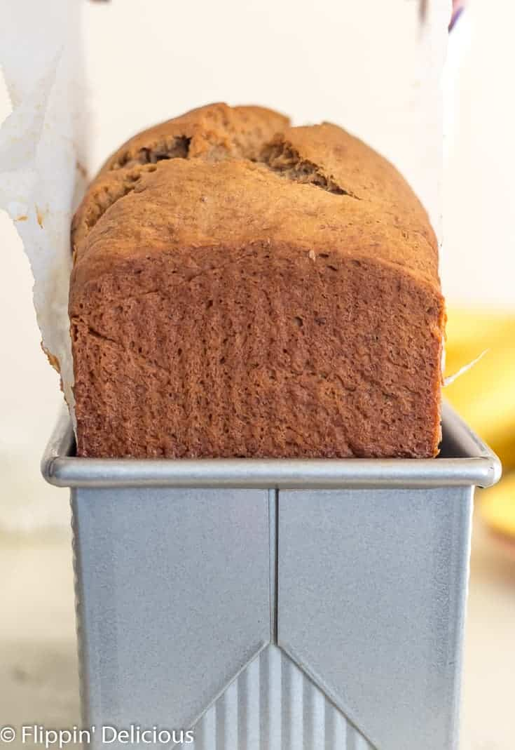 lifting gluten free banana bread from metal 9x4 loaf pan using parchment paper with a bunch of bananas in the background