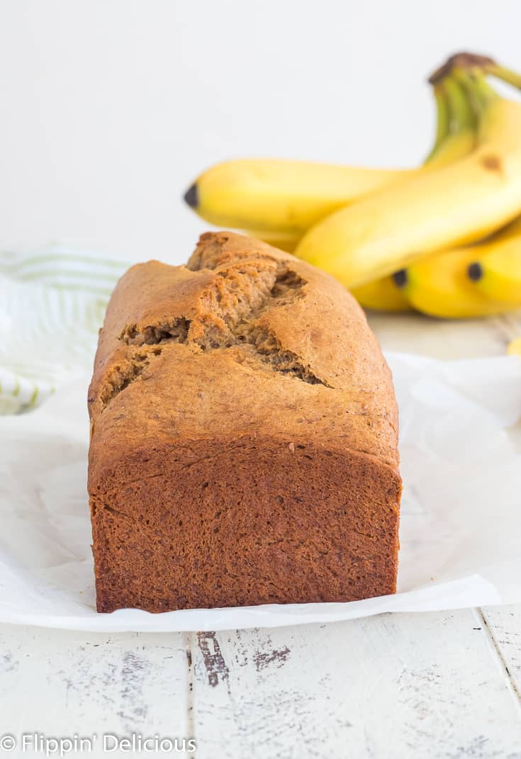 un-sliced loaf of gluten free banana bread on a piece of parchment paper on a white wooden table with a bunch of ripe bananas in the background