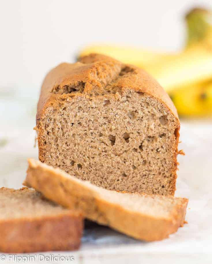 loaf of gluten free banana bread with a few slices in front and out of focus with a bunch of bananas in the background, on a white wooden table