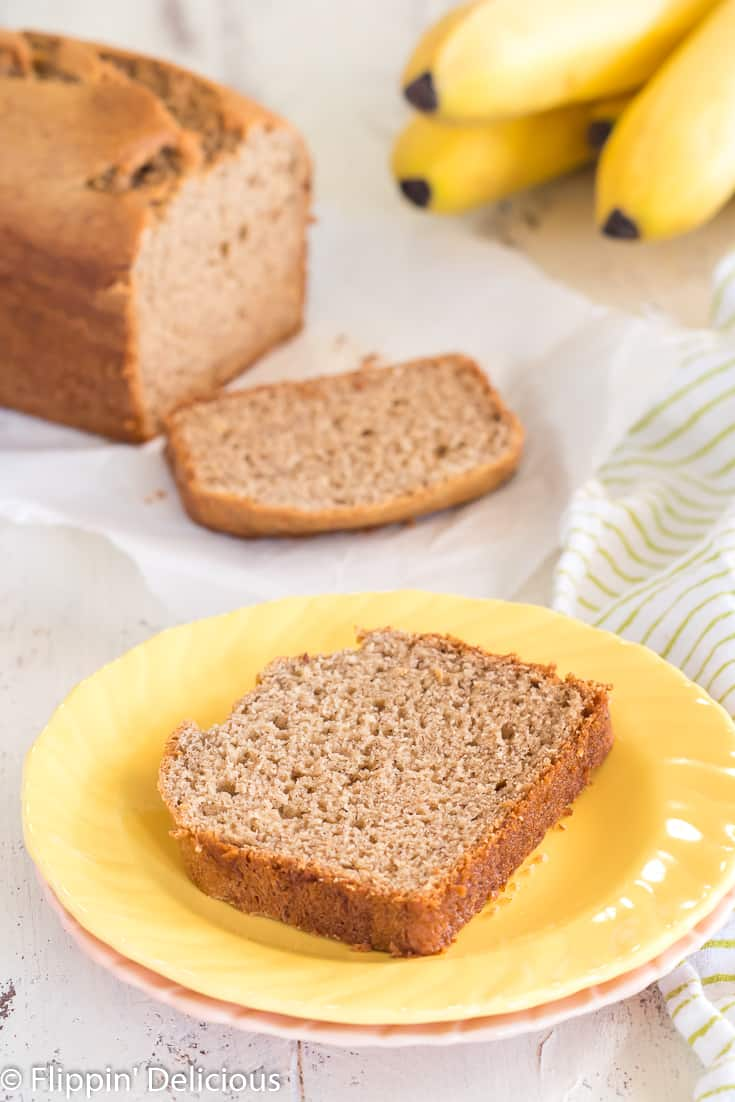 slice of gluten free banana bread on a yellow plate on top with a slice and full loaf of gluten free banana bread and bunch of ripe bananas in the background
