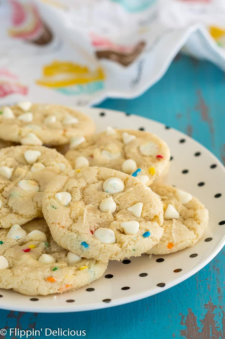 gluten free cookies with white chocolate chips and sprinkles on a cream plate with polka dots on top of a turquoise background with a cupcake dishtowel in the background