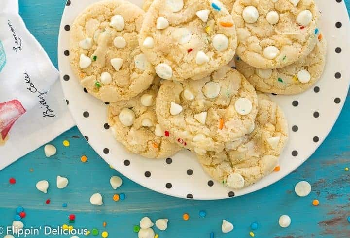 gluten free white chocolate chip cookies with sprinkles on a cream plate with black polka dots on a teal wooden table with white chocolate chips and rainbow sprinkles tossed on it