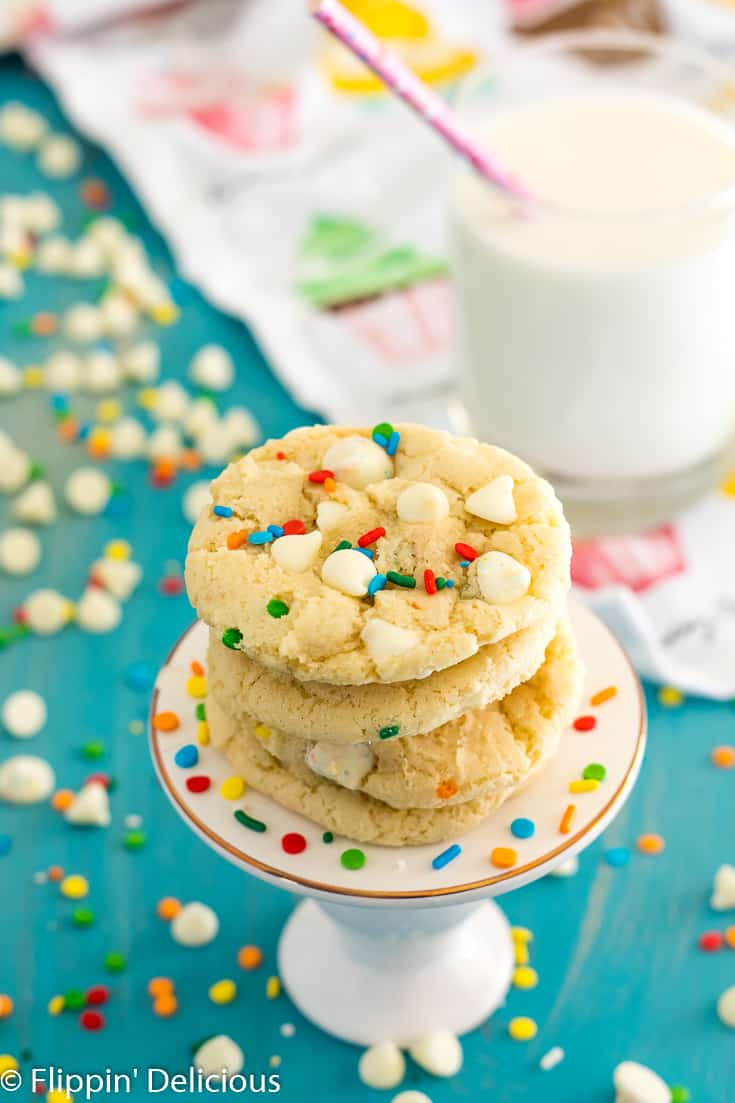 gluten free funfetti cookies with pudding mix on pedestal with white chocolate chips, sprinkles, and a glass of milk in the background