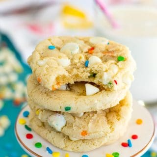 four gluten free funfetti cookies with white chocolate chips, with a bite taken out of the top cookie, on a pedestal on a teal background with a glass of milk, white chocolate chips, more sprinkles, and a dishtowel in the background