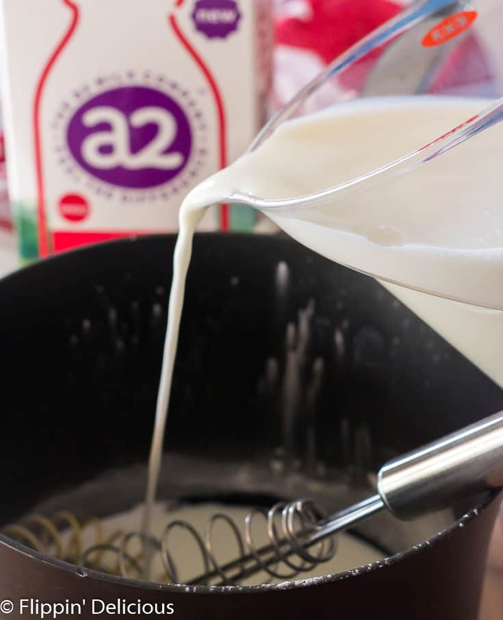 pouring milk into saucepan to make gluten free pudding