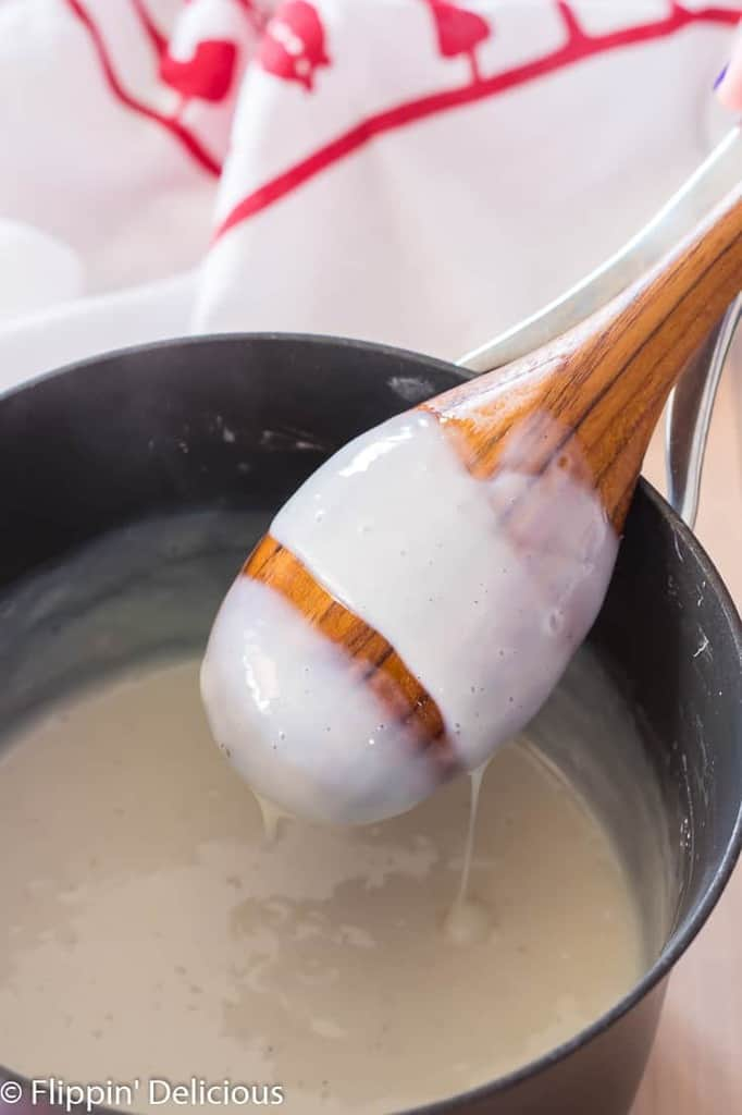 gluten free pudding coating the back of a wooden spoon over a saucepan with dish towel in the back