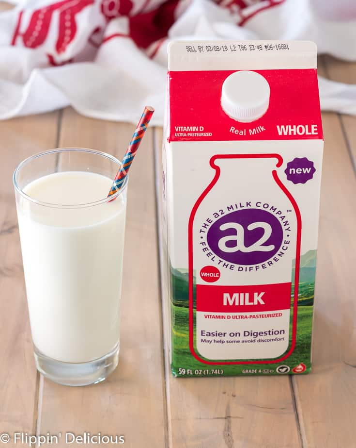 A2 milk in a glass beside carton of A2 milk on a wooden table with a red and white dish towel in the back