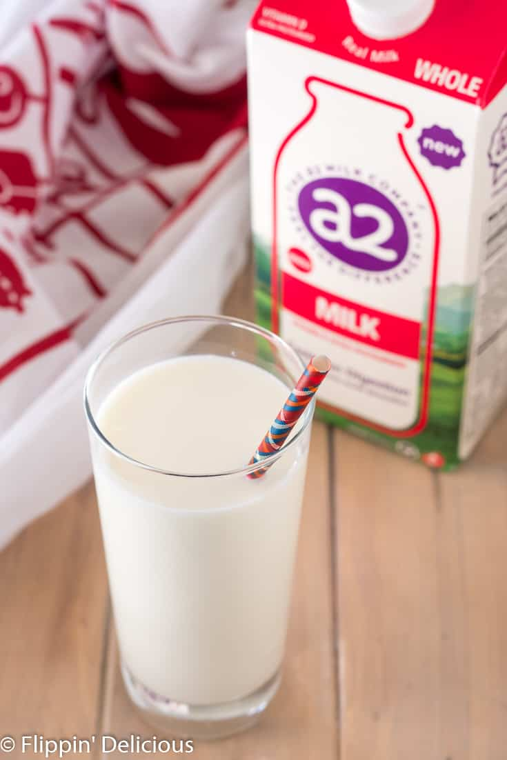 A2 milk in a glass in front of carton of A2 milk on a wooden table with a red and white dish towel in the back
