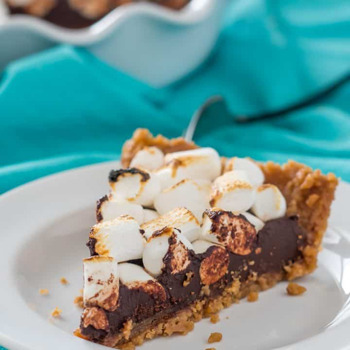 slice of vegan gluten free s'mores fudge pie with toasted marshmallows on a white plate with a teal dish towel and full pie in the background