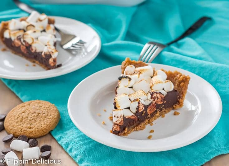 two slices of gluten free s'mores pie on white plates with a teal dish towel and some cookies, dark morsels, and vegan marshmallows