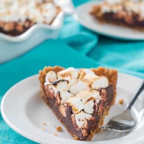 a slice of vegan gluten free s'mores pie with toasted marshmallows on a white plate with a fork, on a teal dish towel with a full pie and remaining slice in the background.