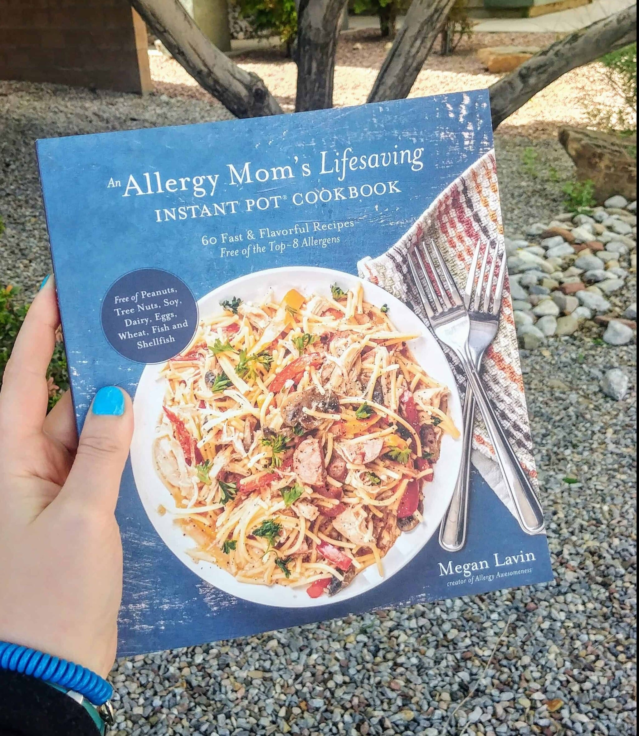 hand with blue nails holding an allergy mom's lifesaving instant pot cookbook