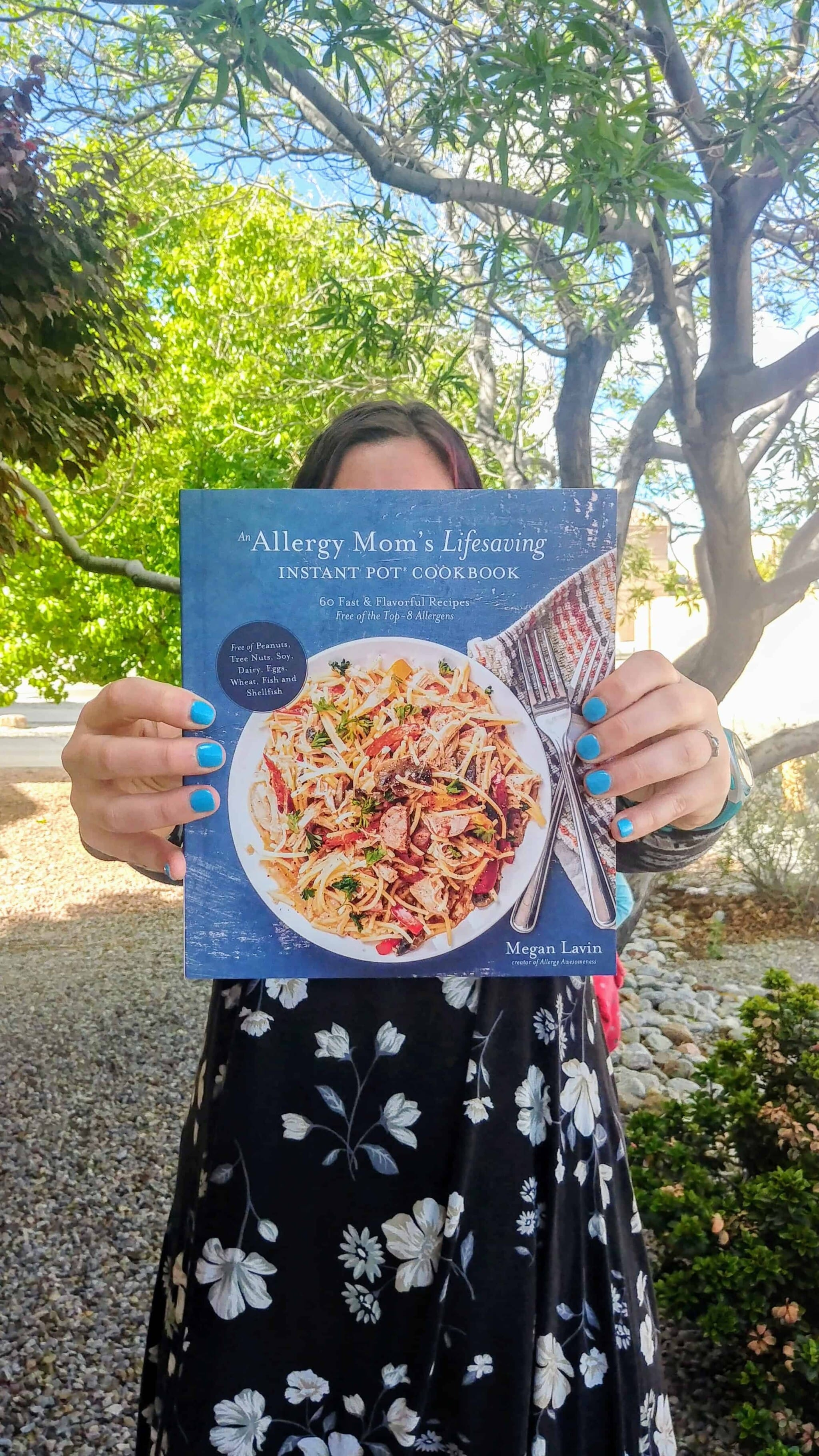 woman in dress with hand with blue nails holding an allergy mom's lifesaving instant pot cookbook in front of her face
