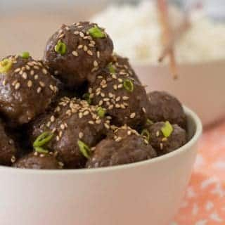close up of gluten free teriyaki meatballs in a bowl garnished with sesame seeds and green onions with a blurry bowl of rice with chopsticks in the background.
