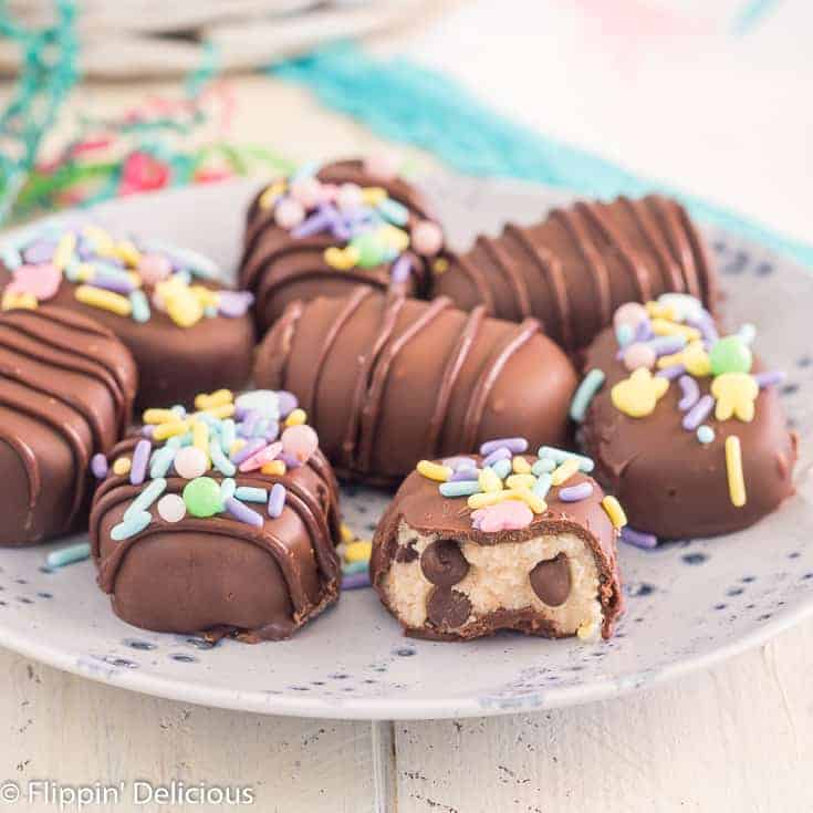 gluten free cookie dough truffles shaped like eggs, covered in chocolate on a periwinkle plate on a white table with easter grass and basket in the background