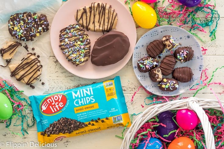 overhead of big and small gluten free chocolate covered cookie dough easter eggs on a white table with easter grass, easter basket, and a bag of Enjoy LIfe Mini Chips