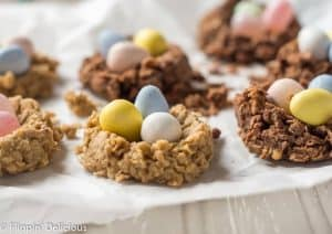 sunflower seed butter and chocolate no bake oatmeal cookie birds nest with chocolate eggs and jelly beans on a piece of parchment paper on a grey table