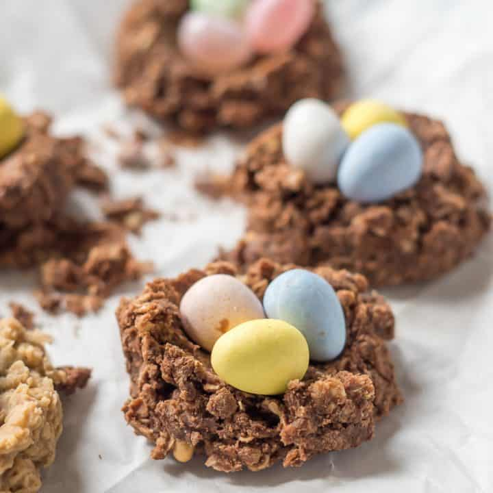 chocolate sunflower seed butter oatmeal gluten free no bake cookie birds nest with chocolate eggs inside on a white parchement paper