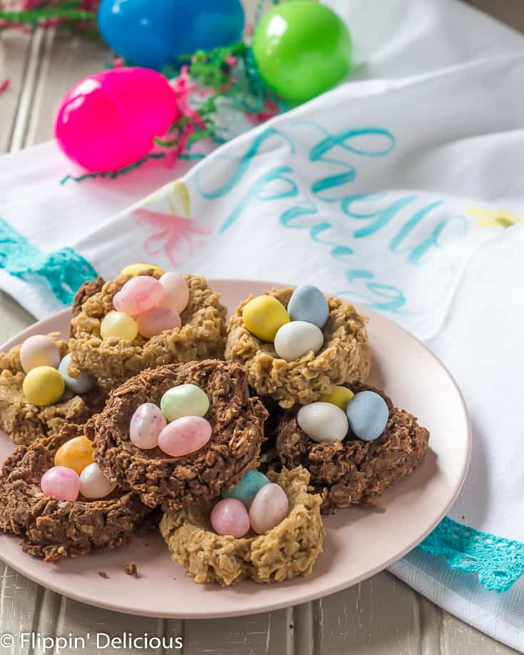 gluten free birds nest cookies on a pink plate on a gray table with a spring tea towel and bright green pink and blue plastic easter eggs