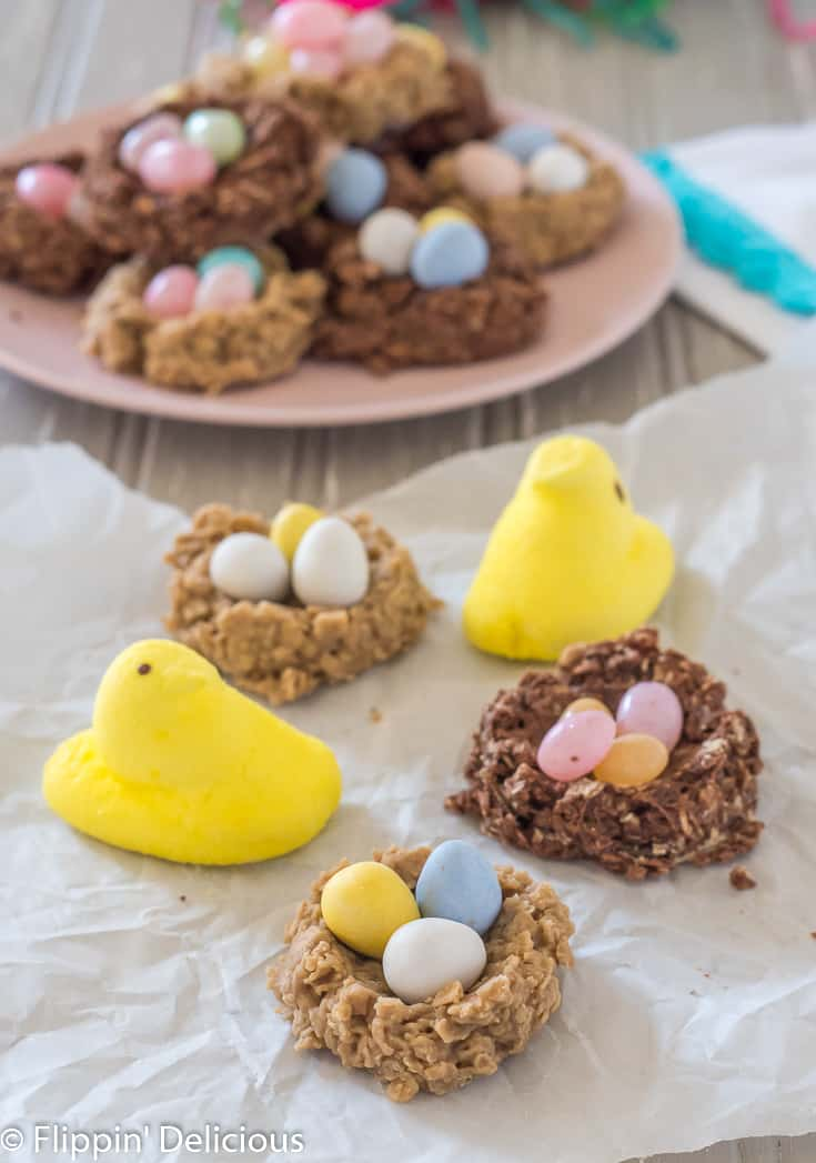 gluten free no bake birds nest cookies with mini eggs and peeps on a piece of parchment paper with a pink plate full of more birds nest cookies in the background