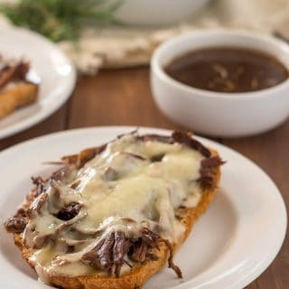 open face gluten free french dip sandwich on a white plate with a small white dish of au jus and another sandwich in the background
