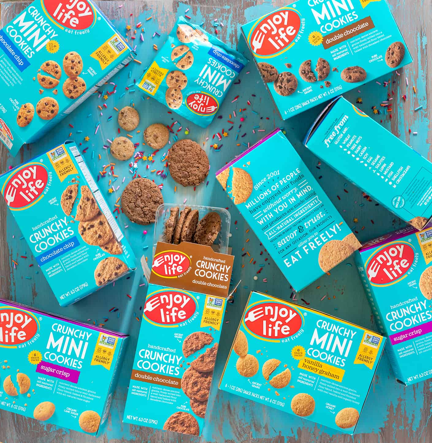 overhead of enjoy life crunchy cookies and mini cookies in packaging on a teal table, with sprinkles spilled all over