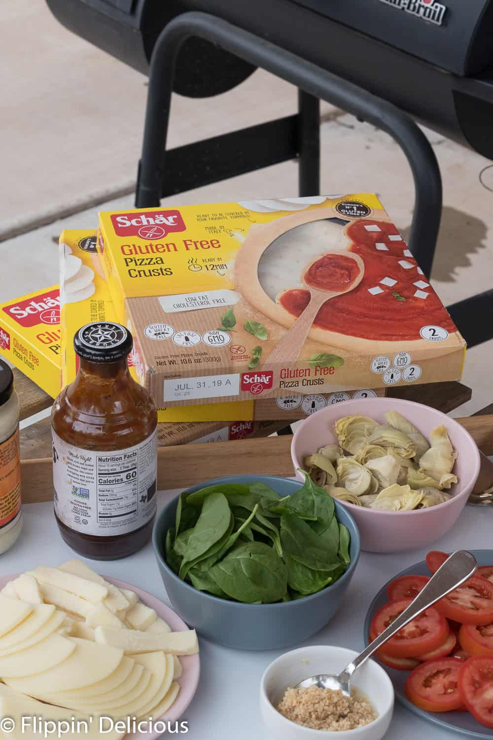 schar gluten free pizza crusts among pizza toppings with a grill in the background