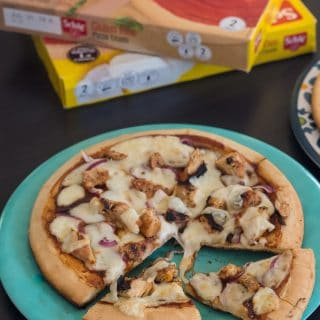gluten free grilled barbecue chicken pizza on a blue plate with two slices cut out