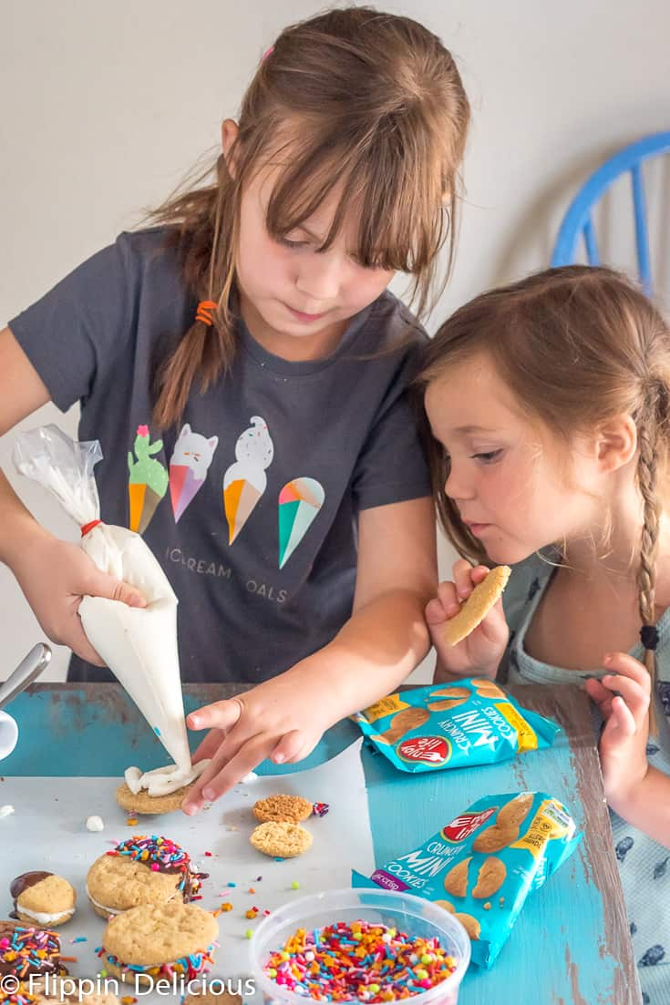 older girl showing younger sister how to pipe oreo style cream filling onto a cookie to make gluten free sandwich cookies