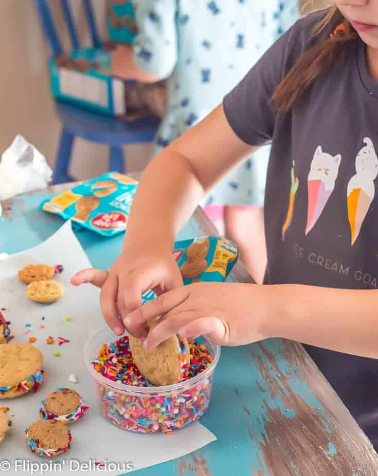 young girl rolling gluten free sandwich cookie to coat edges in sprinkles