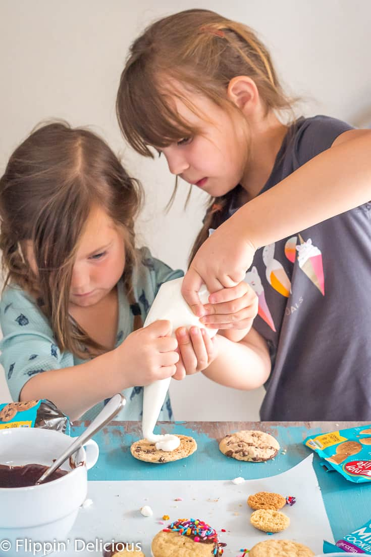 young girl filling gluten free sandwich cookie with oreo style cream filling, with big sister helping her hold the piping bag