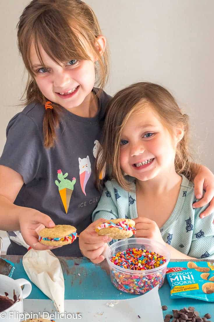 two girls holding gluten free sandwich cookies with oreo-style cream filling rolled in rainbow sprinkles with gold stars.