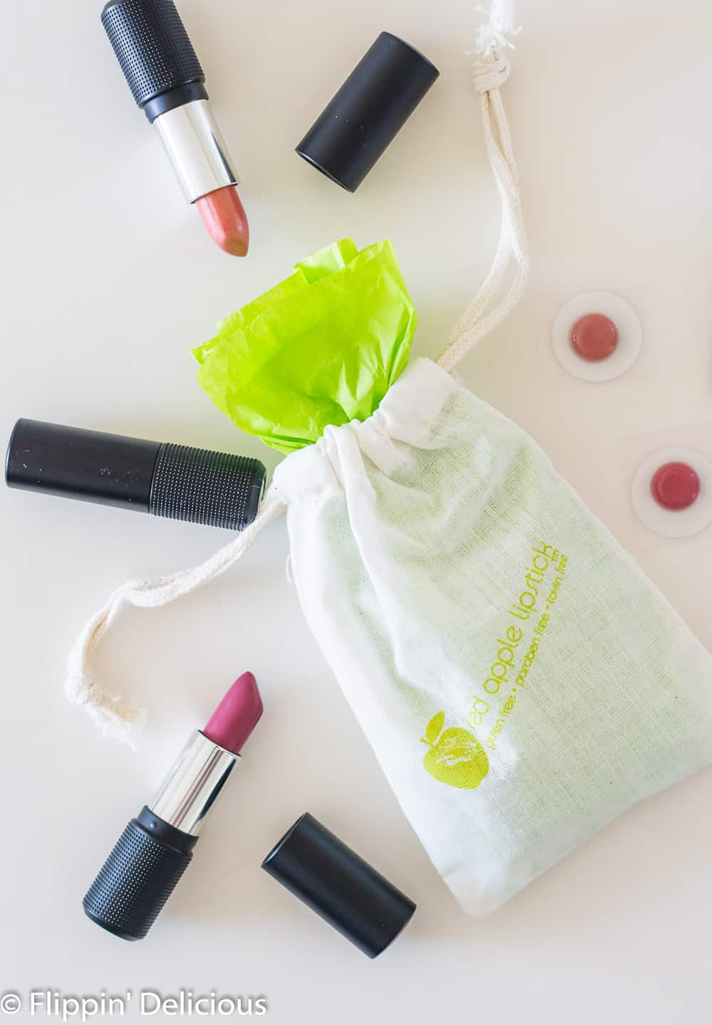 overhead of red apple lipstick drawstring bag filled with gluten free lipstick wrapped in green tissue paper with open gluten free lipsticks beside it, all on a white counter