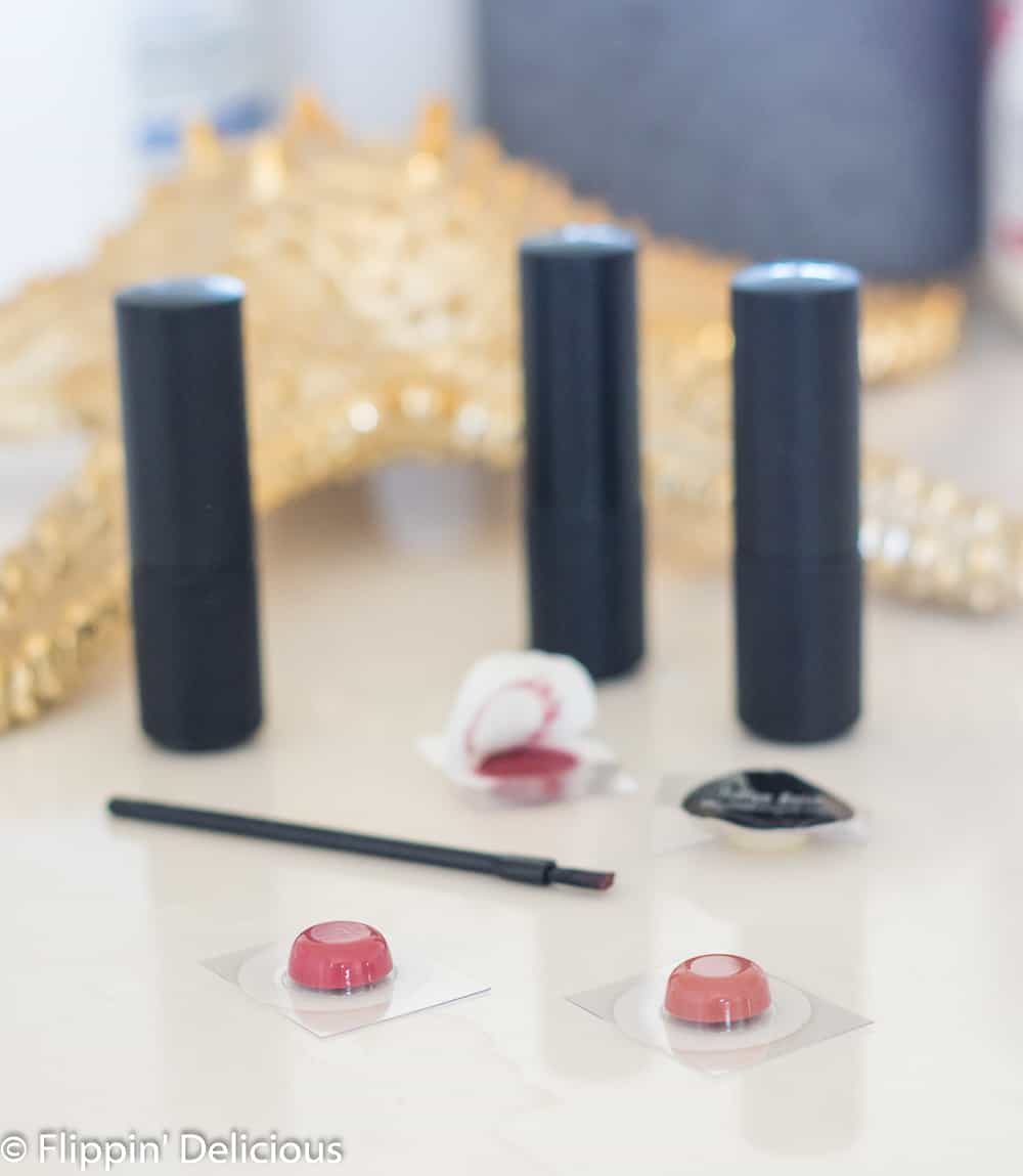 samples of gluten free lipstick from red apple lipstick on a white counter with tubes of red apple lipstick, and a tiny lipstick brush with a golden starfish and blue jar in the background