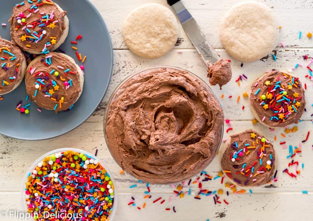 overhead bowl full of fluffy vegan chocolate frosting on a white wooden table with a plate of gluten free sugar cookies being frosted and a tub of rainbow sprinkles.