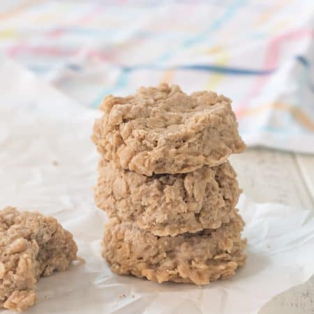 stack of three gluten free peanut butter oatmeal no bake cookies on parchment paper with another cookie with a bite taken out of it, with a pastel plaid dish towel in the background