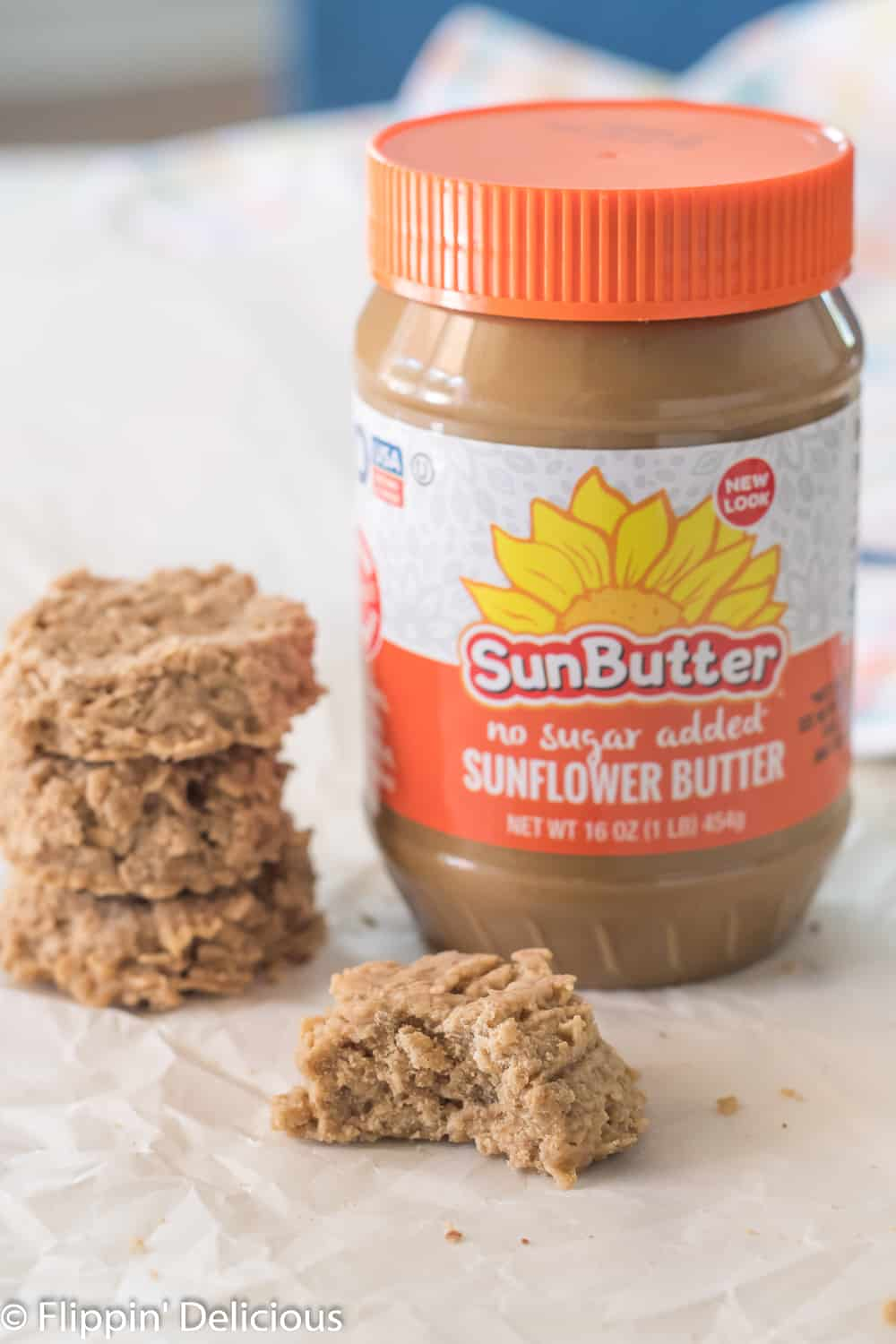 three gluten free no bake cookies with sunbutter stacked on top of each other beside another cookie with a bite take out on a piece of white parchment paper with a jar of SunButter