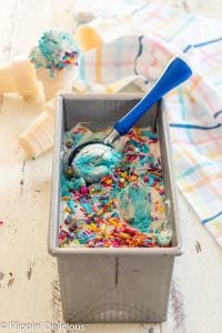 metal loaf pan full of no churn dairy free cake batter ice cream with scoop being taken out by a blue-handled ice cream scoop with gluten free ice cream cones in the background