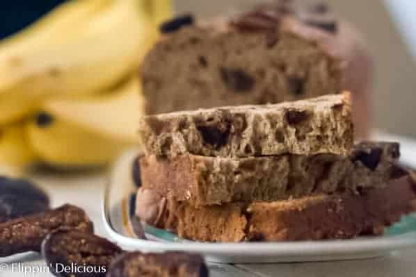 stack of three slices of gluten free fig banana bread on a plate, with the remaining gluten free banana bread with figs in the background. On a white table, with some sliced dried figs and a bunch of yellow bananas in the background