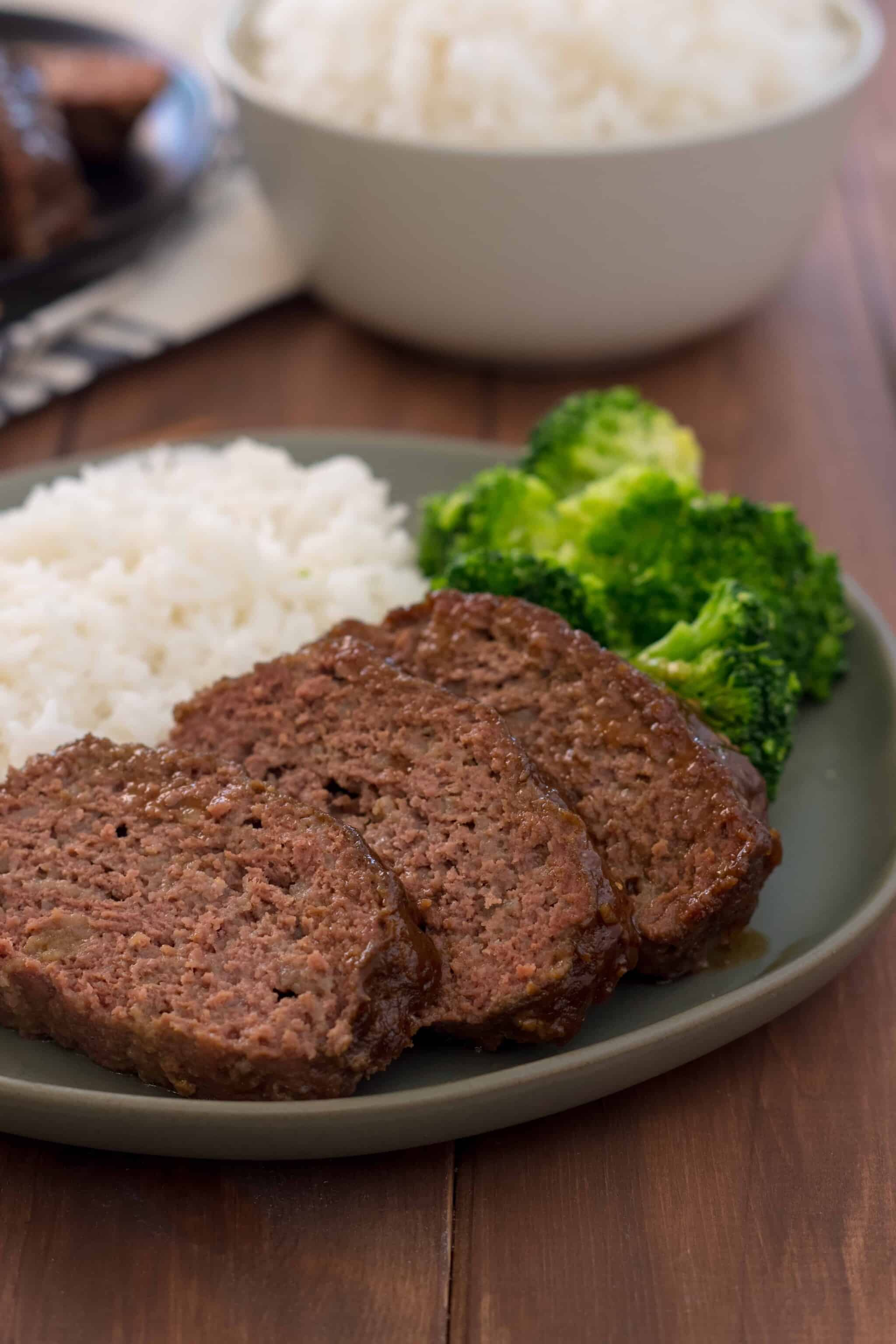 green plate with sliced gluten free instant pot teriyaki meatloaf, white rice, and broccoli