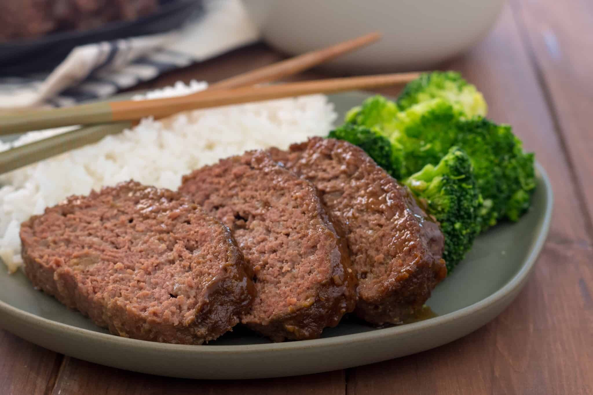 gluten free instant pot meatloaf glazed with teriyaki on a green plate with rice and broccoli