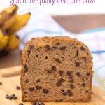 "loaf of gluten free banana bread with chocolate chips on a cutting board with ripe bananas in the background with text ""chocolate chip banana bread gluten-free