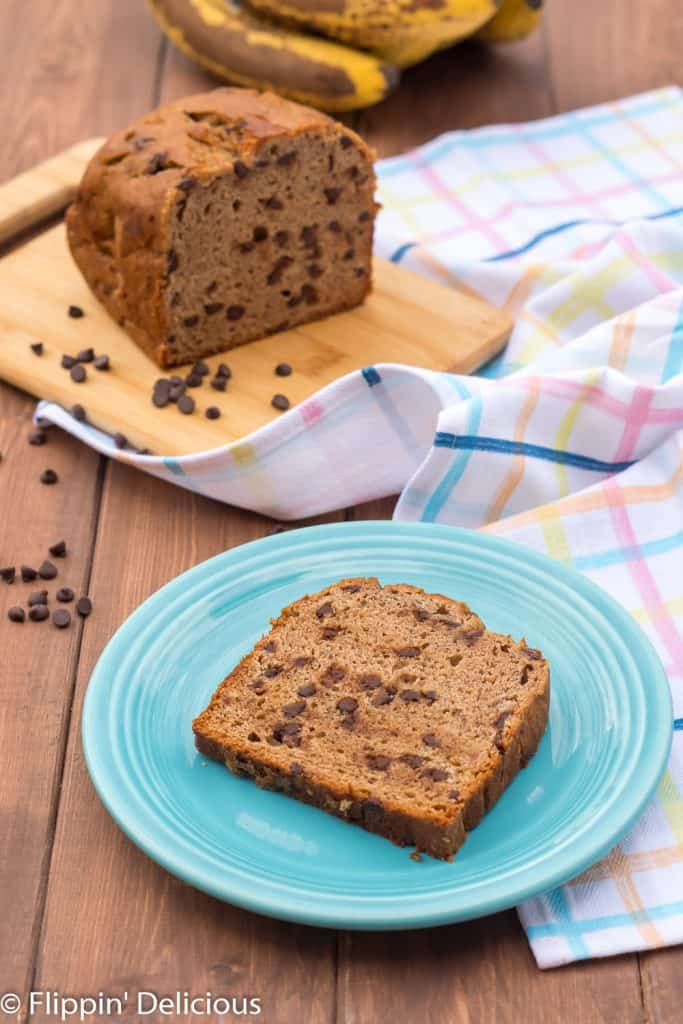 Slice of gluten free chocolate chip banana bread on a turquoise plate with a loaf of gluten free banana bread with chocolate chips in the background