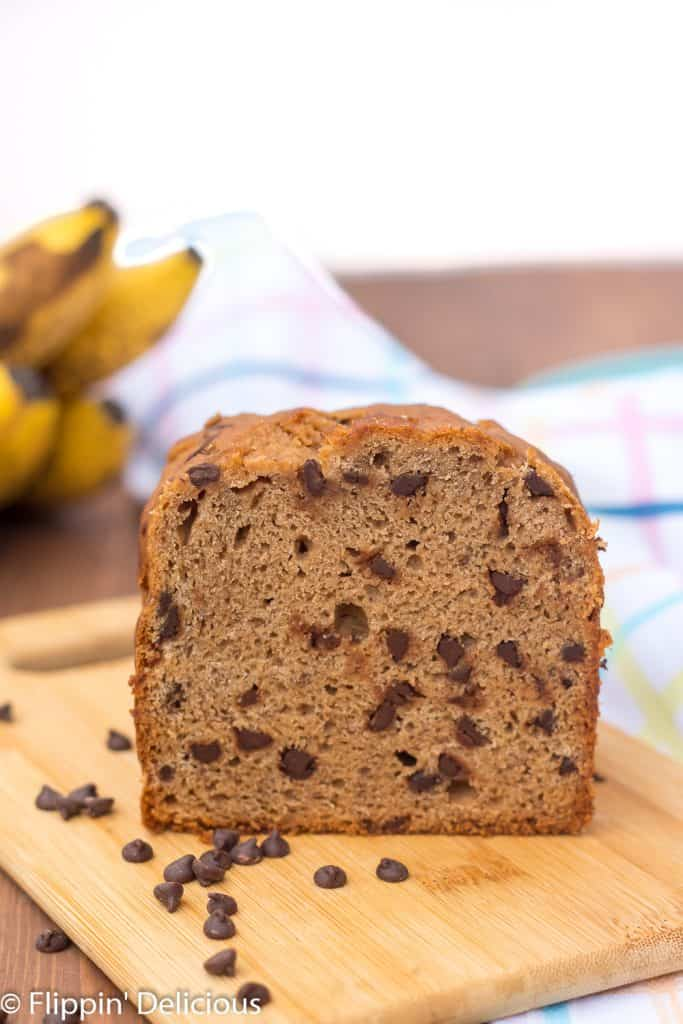 loaf of gluten free banana bread with chocolate chips on a cutting board with ripe bananas in the background